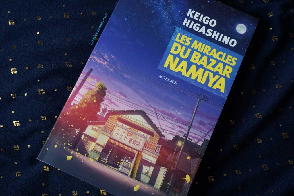 Photographie du roman Les Miracles du Bazar Namiya par Keigo Higashino aux éditions Actes sud sur fond bleu marine et doré